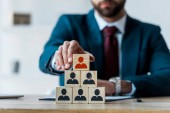 selective focus of wooden cubes near bearded recruiter in office