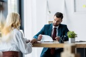 selective focus of handsome recruiter looking at blonde employee