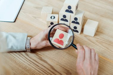 cropped view of woman holding magnifier near wooden cube