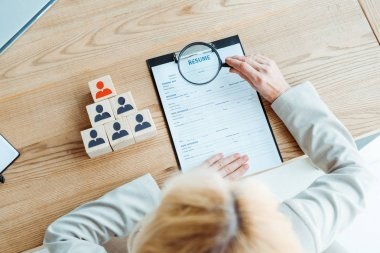 selective focus of blonde recruiter holding magnifier near clipboard