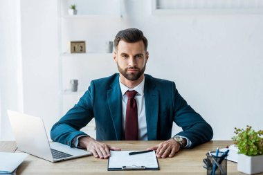 Handsome recruiter sitting near clipboard and laptop in office stock vector