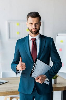 handsome recruiter standing and holding clipboard with resume letters while showing thumb up