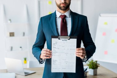 cropped view of bearded recruiter in suit standing and holding clipboard with resume letters