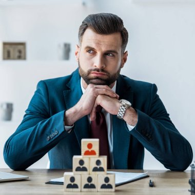 selective focus of pensive and bearded man with clenched hands near wooden cubes