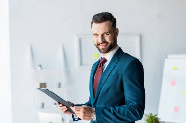 cheerful bearded man in suit holding clipboard in office