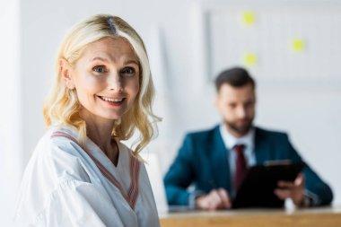Selective focus of happy blonde employee near recruiter stock vector