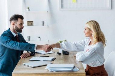 Selective focus of handsome recruiter and attractive employee shaking hands stock vector