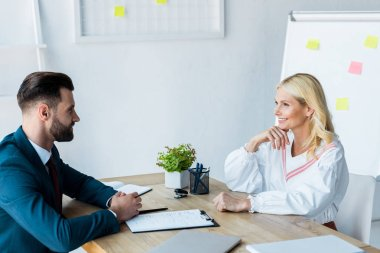 happy blonde woman looking at handsome recruiter with clenched hands