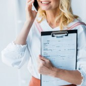 cropped view of happy woman talking on smartphone and holding clipboard with resume letters