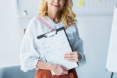 cropped view of happy blonde woman holding clipboard with resume letters
