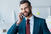 cheerful bearded man in suit talking on smartphone in office