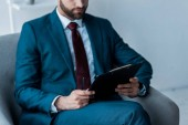 cropped view of bearded man sitting in armchair with clipboard