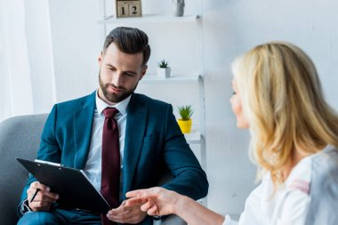 selective focus of handsome recruiter with clipboard near woman pointing with finger