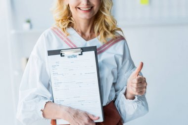 Cropped view of happy blonde woman holding clipboard with resume letters and showing thumb up stock vector