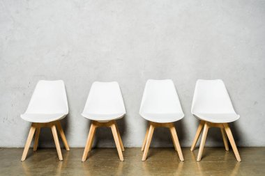 white chairs near grey concrete wall with copy space in office