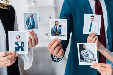 Cropped view of recruiters touching photos while standing in office stock vector