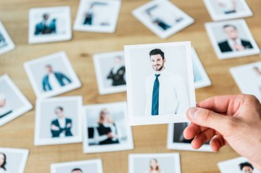cropped view of recruiter holding photo with man in suit