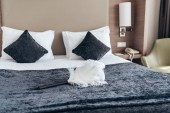 Photo white duster on bed with pillows in hotel room
