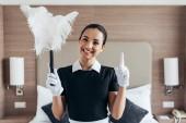 přední pohled na usmívající se služebnou v bílých rukavicích s dusterem a s nápadem u postele v hotelovém pokoji