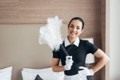 front view of smiling maid in white gloves holding duster near bed and looking at camera
