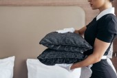 abgeschnittene Ansicht der Magd in weißen Handschuhen halten Kissen im Hotelzimmer