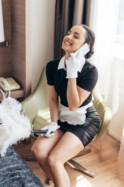 Smiling pretty maid in white gloves holding duster and talking on smartphone in hotel room stock vector