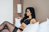 sexy brunette girl in black stockings and underwear lying in bed