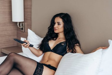 sexy girl in black lingerie holding remote controller in bedroom
