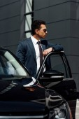 african american businessman in suit and sunglasses standing near car at sunny day