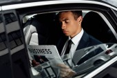 african american businessman in suit reading newspaper in car