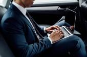 Ausgeschnittene Ansicht eines afrikanisch-amerikanischen Geschäftsmannes mit Laptop im Auto