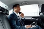 Afrikanisch-amerikanischer Geschäftsmann im Anzug benutzt Laptop während er im Auto mit dem Smartphone spricht
