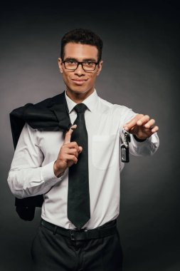 smiling african american businessman holding blazer and car keys on dark background