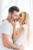 woman kissing and embracing man at home in morning