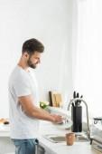 hezký muž umývání nádobí v kuchyni ráno