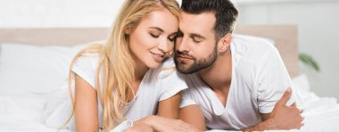 panoramic shot of beautiful couple with eyes closed resting on bed at home