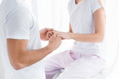 partial view of couple in pajamas holding hands at home