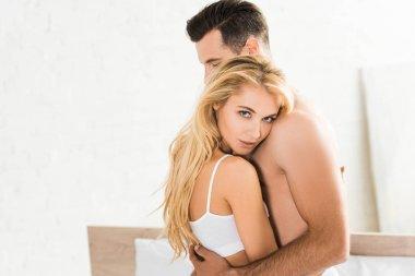 beautiful woman embracing man and looking at camera at home in morning