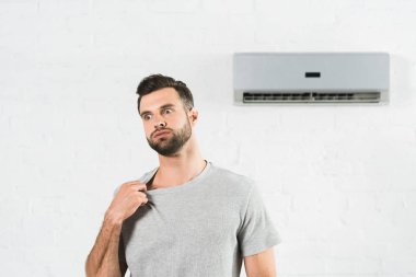 handsome man suffering from heat under air conditioner at home