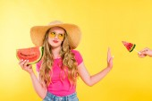 nespokojena dívka s melounem, který gestikuluje a odmítá lízátku na žluté