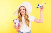 beautiful girl with plane model and air tickets On yellow