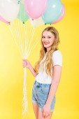 Fotografie beautiful girl with balloons looking at camera and smiling On yellow