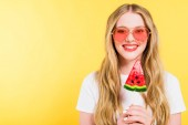 beautiful smiling girl with lollipop in shape of watermelon On yellow