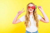 beautiful happy girl in sunglasses with lollipop in shape of watermelon doing Peace Sign On yellow