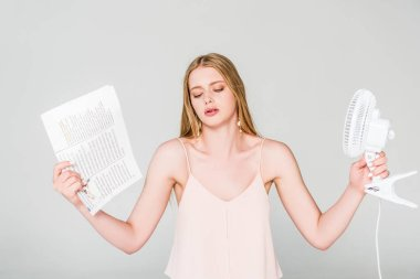 beautiful young woman with Electric Fan and newspaper suffering from heat on grey