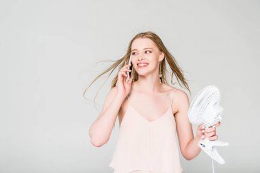 Beautiful young woman with Electric Fan suffering from heat and talking on smartphone isolated on grey stock vector