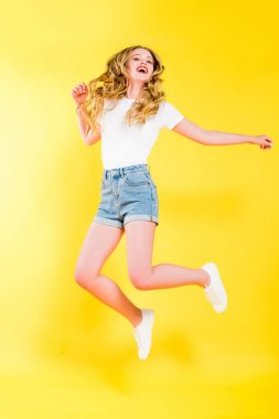 Beautiful happy blonde young woman jumping On yellow stock vector