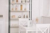 lehká kuchyně s laptopem na bílém stolku, židle a stojan se sklenkami
