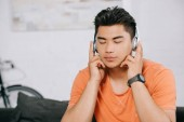 Photo dreamy asian man listening music in headphones with closed eyes