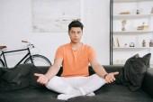 mladý asijský muž meditující, když sedí v lotosové pozici na pohovce doma